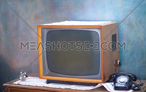 Vintage retro look living room detail. Television, telephone and clock on wooden old table