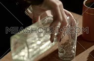 female hands pouring water in a transparent glass in slow-motion