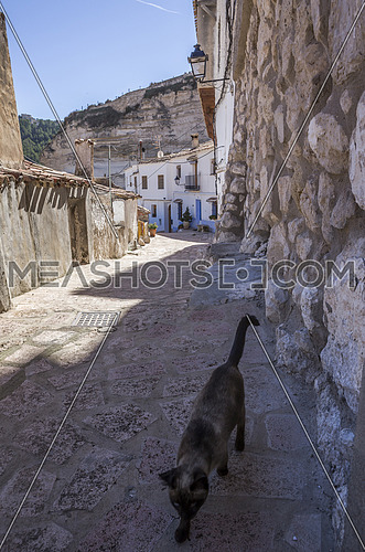 Alcala del Jucar, Spain - October 29, 2016: Narrow street with white painted houses, typical of this town, take in Alcala of the Jucar, Albacete province, Spain