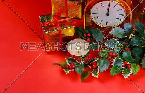 Christmas and New year clock decorations on burning candle, decorations, on red background
