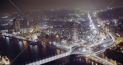Aerial Shot from drone flying toward over the River Nile showing Bridge, Hilton Hotel and Television Network Building in cairo at night
