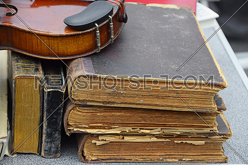 Close up stack of old vintage antique books and violin for sale at flea market retail display, high angle view