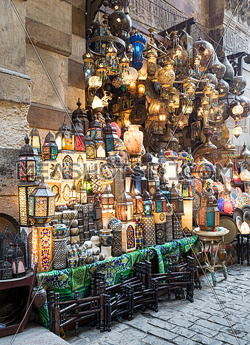 Huge group of stacked illuminated copper lanterns over background of old decorated stone wall and basalt tiles floor at Khan El Khalili bazaar