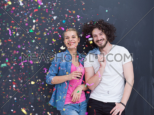 handsome young couple celebrating new year and chrismas party while blowing confetti decorations to camera isolated over gray background