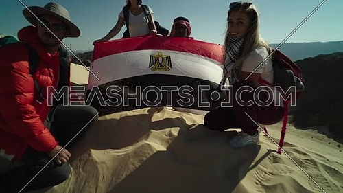 Track out shot for group of tourists and bedouin guide spreading Egyptian flag while exploring Sinai Trail from Ain Hodouda at day.