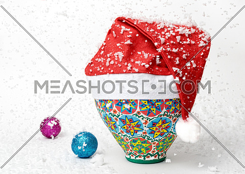 Egyptian decorated colorful pottery vase wearing Santa Claus red hat on white background with two colored shining Christmas balls and falling snow