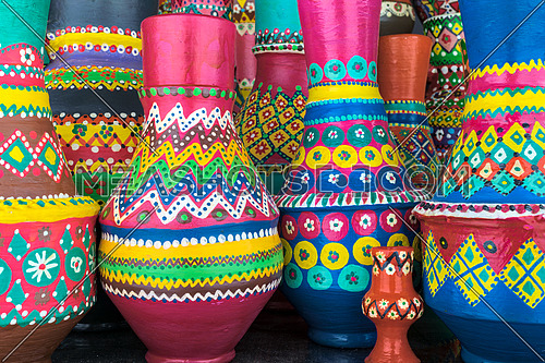 Front view of a composition of artistic painted colorful handcrafted pottery vases