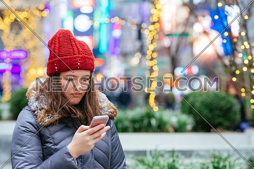 Girl walking and texting on her smartphone in the street wearing a red hat