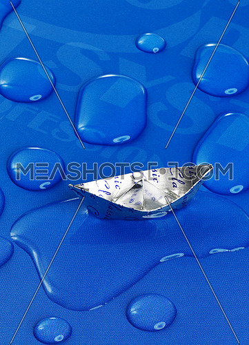 paper boat floating on water drops ,over blue background
