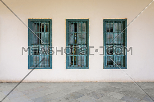 White wall with three grunge windows with wooden green shutters and wrought iron bars and white marble floor