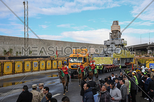 Long shot for The Statue of King Ramses II in the transferring machine at arrival time at the Grand Egyptian Museum in Cairo while people are taking photos for the statue and ceremony Soldiers are riding horses around the statue on 25 January 2018