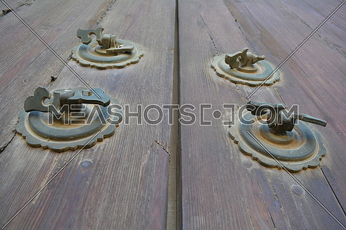 A detailed close up of a rustic door with copper handles