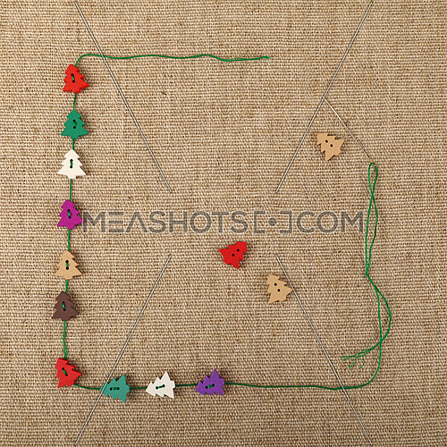 Festive template of handicraft colorful wooden Christmas tree button decorations and thread over linen canvas, close up, elevated top view, copy space