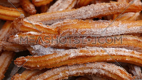 Sweet fresh churros with sugar, traditional Spanish or Portuguese deep fried dough pastry snack cooked close up, high angle view