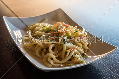 delicious japanese food yaki udon, noodles with seafood,shrips and vegetables,white plate on wooden backgroung.