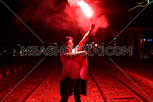 Young man cheering for egypt in the street at night holding a firework and big egyptian flag in korba area at night