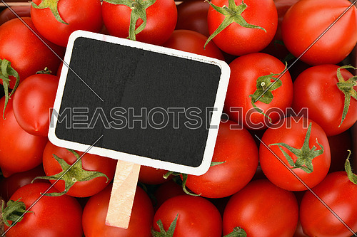 Red ripe fresh small cherry tomatoes background with black wooden chalkboard price sign tag close up, top view