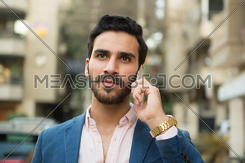 A young man is talking on a mobile phone in the street