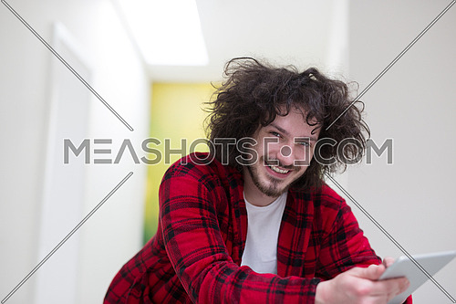 young freelancer in bathrobe working from home using tablet computer