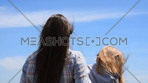 Close up, rear view of young woman and small girl over clear blue sky, wind shaking hair, sunny day, low angle view