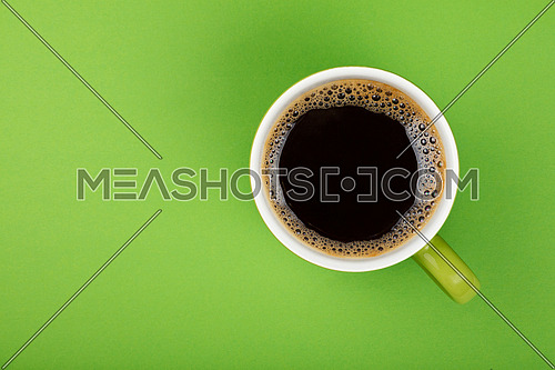 One full morning Americano black coffee with froth edge in big green cup with saucer on green paper background, top view
