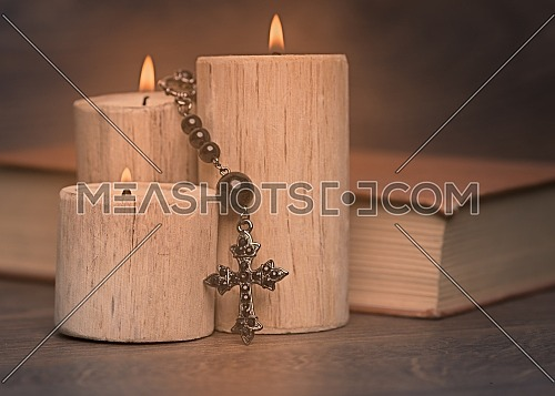 black rosary and crucifix resting on closed book near the candles on wooden table, religion school concept. Vintage style.
