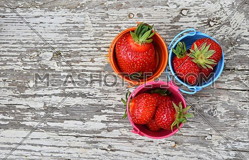 Three small colorful multicolored metal toy buckets full of red mellow strawberries on old vintage wooden table, top view, close up