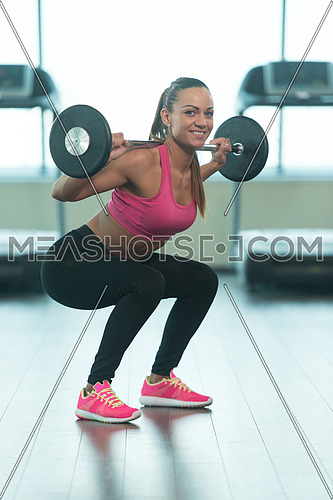 Young Woman Working Out Legs With Barbell In A Gym - Squat Exercise