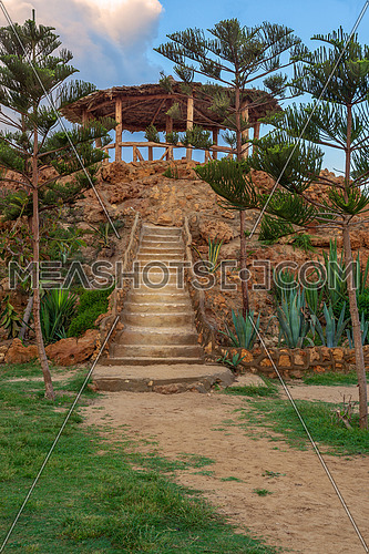 Natural stone stairway with green bushes on both sides leading to wooden pergola with partly cloudy sky at Montaza Park in summer, Alexandria, Egypt