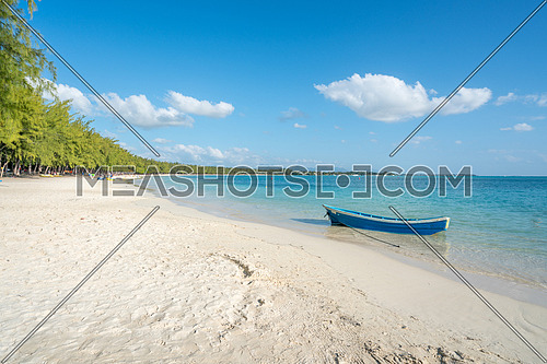 Fish boat on blue sea and  paradice beach  with white sand at Mauritius island.