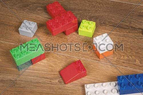 view on colorful toy bricks on a brown wooden background. Toys in the table