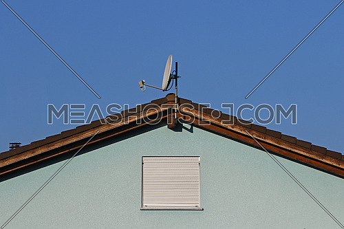 Blue on blue facade with simple window, ceramic tile roof line and satellite dish