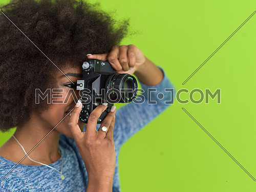 portrait of a smiling pretty african american girl taking photo on a retro camera isolated over green background