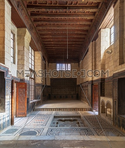 Hall at ottoman era historic house of Moustafa Gaafar Al Seleehdar located at Al Darb Al Asfar District, Cairo, Egypt with decorated wooden ceiling, marble decorated floor and ornate stone walls
