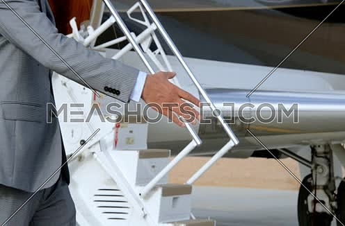 Business men handshaking in front of private jet