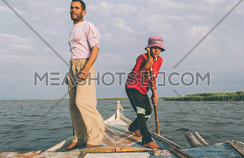 a man and his kid taking thier canoe in a windy morning to catch fish in