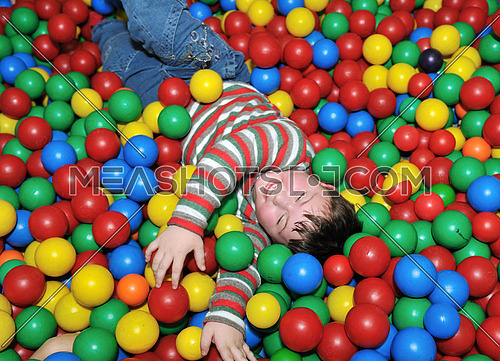 happy child playing in colorful balls pool