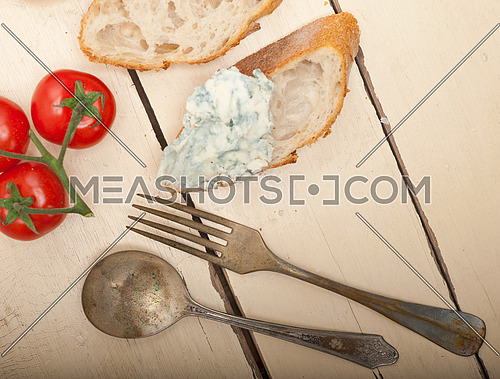 fresh blue cheese spread ove french baguette with cherry tomatoes on side