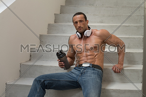 Muscular Mature Man Drinking A Water Bottle