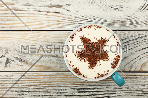 Close up blue cup full of latte cappuccino coffee with star shaped chocolate on milk froth over background of white vintage wooden planks table, close up, elevated top view, directly above
