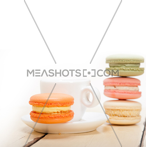 colorful macaroons with espresso coffee over white wood table