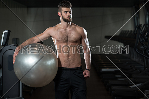 Portrait Of A Young Sporty Man In The Modern Gym With Exercise Ball