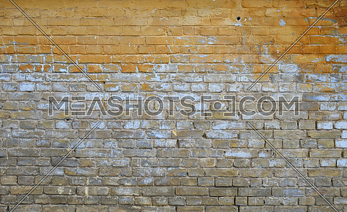 Old grunge vintage yellow and brown painted brick wall with blue and white paint stains and dirt faded background
