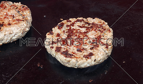Close up beef meat burger for fast food hamburger cooked on barbecue grill, high angle view