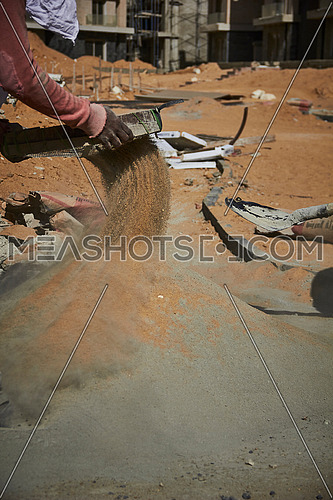 Mid Shot for worker sifting Cement in a construction site at day