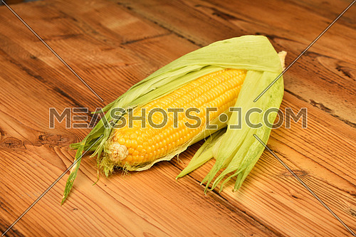 One open fresh yellow corn cob with green husk on brown vintage wooden surface