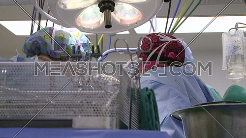 Low angel shot for medical team performing surgery and surgical tray in foreground
