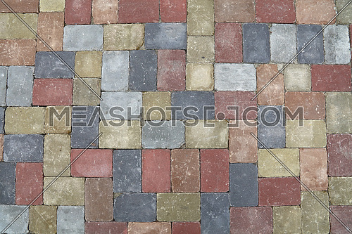Background of street road colorful stone paving of multicolor bricks, close up, top view, high angle, directly above