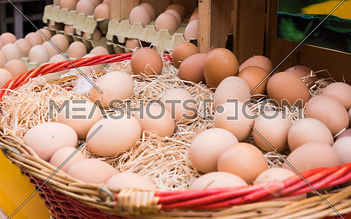 Brown chicken eggs leaning on straw in wooden basket at matket,outdoor.