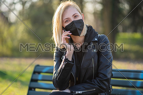 Woman using a Smart phone in the park sitting on a bench in a park on a sunny day, wearing black medical mask for protection, during Covid-19 quarantine.